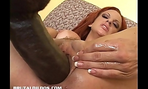 Busty redhead fills her pink pussy with a burly dildo